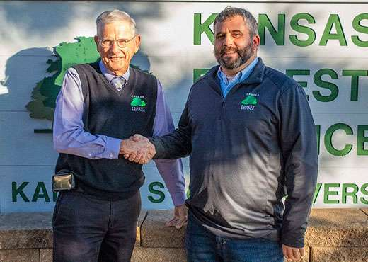 Outgoing Kansas Forest Service state leader Larry Biles (left) shakes hands with Jason Hartman, who will take over the agency's top job on Dec. 29.