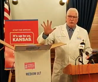 During a news conference Wednesday, KDHE Secretary Dr. Lee Norman shows the packaging container used to ship the vaccine to the state from Pfizer. It contains a probe to monitor the cold temperature necessary to store the vaccine.