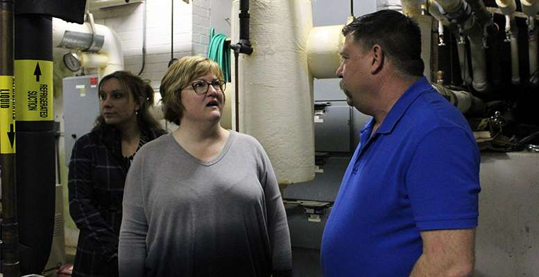 Board member Tammy Wellbrock discusses the HVAC system with Buildings and Grounds Director Rusty Lindsay in the O'Loughlin boiler room during a tour of the building Monday night.