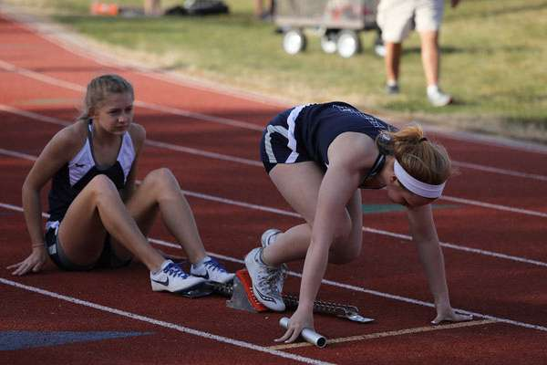 MK Dwyer, TMP senior, in the blocks, with Emily Shippers sitting, is disappointed she will miss her senior year of track at TMP.