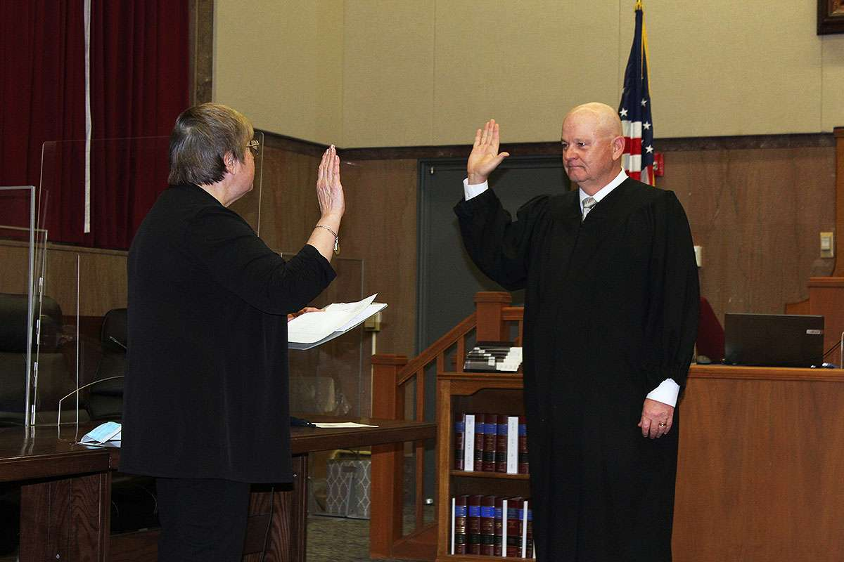 Outgoing Ellis County Clerk Donna Maskus swears 23rd Judicial District Judge Glenn Braun into office on Monday.